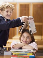 Kinder im Klassenzimmer, Junge mit Buch über Kopf des Mädchens