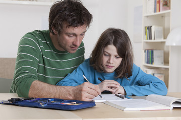 Deutschland, Bayern, München, Vater hilft Sohn bei den Hausaufgaben