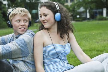 Deutschland, Berlin, Teenager-Paar mit Kopfhörer, Musik hören im Park