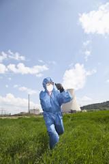 Deutschland, Bayern, Unterahrain, Mann mit Schutzkleidung läuft in Feld am AKW Isar