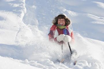 Österreich, Land Salzburg, Flachau, junge Frau reitet auf Schlitten im Schnee