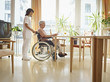 Deutschland, Köln, ältere Frau, Seniorin liest Zeitung im Rollstuhl