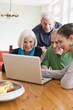 Deutschland, Leipzig, Männer und Frauen schauen Bilder auf Laptop