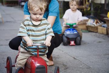 Deutschland, Berlin, Mutter und Junge auf Spielzeug-Traktor