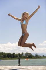 Junge Frau springt auf Steg, Bikini