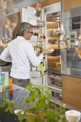 Deutschland, München, erwachsener Mannstellt Schüssel in Kühlschrank