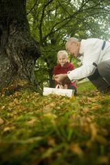 Deutschland, Baden-Württemberg, Schwäbische Alb, Großvater und Enkelin suchen Pilze im Wald