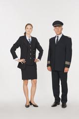 Pilot und junge Stewardess vor weißem Hintergrund