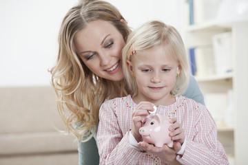 Deutschland, Bayern, München, Mutter und Tochter mit Sparschwein