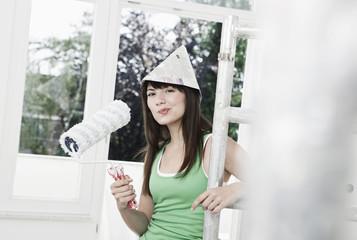 Deutschland, Köln, Junge Frau trägt Papierhut, Gerüst, , Wohnungsrenovierung