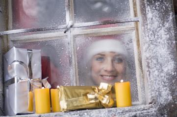 Österreich, Salzburger Land, junge Frau schaut durch Fenster, Pakete und Kerzen auf der Fensterbank