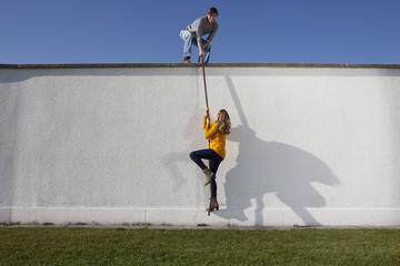 Deutschland, Bayern, München, Junges Paar Kletterwand
