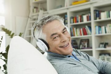 Deutschland, Berlin, erwachsener Mann mit Kopfhörer auf der Couch