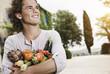 Italien, Toskana, Magliano, Junger Mann hält Vielzahl von Gemüse, lächeln