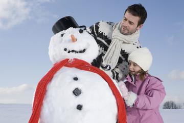 Deutschland, Bayern, München, Vater und Tochter mit einem Schneemann