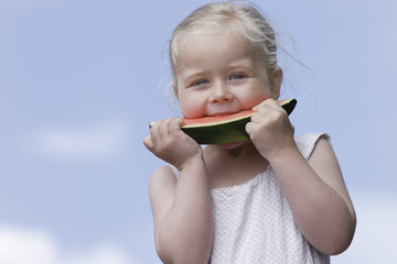 Deutschland, Bayern, Mädchen isst Stück Wassermelone