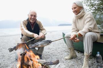 Deutschland, Bayern, Walchensee, älteres Paar, Senioren sitzt am Lagerfeuer, Grillen von Fisch
