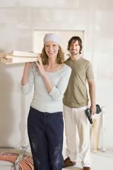 Junges Paar tragen Holzbohlen herum
