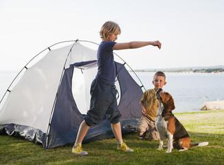 Kroatien, Zadar, Mädchen und Jungen spielen mit Hund vor der Zelt am Strand