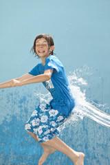 Deutschland, Junge springendd im Wasser vor blauem Hintergrund