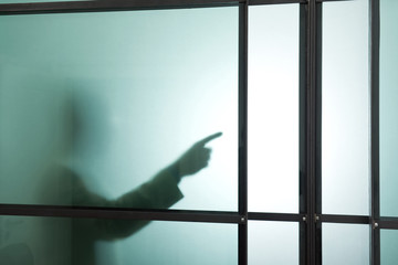 Deutschland, München, Silhouette eines Geschäftsmanns hinter Milchglas, gestikulierend