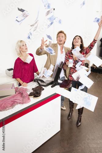 Paar im Laden wirft Banknoten in die Luft