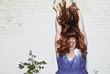 Deutschland, Berlin, Junge Frau springt in der Nähe einer Wand, lachen