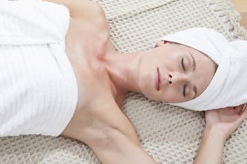 Junge Frau im Handtuch eingewickelt auf Bett liegend