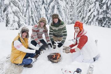 Österreich, Salzburg, Männer und Frauen sitzen am Feuer im Winter