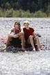 Deutschland, Bayern, Tölzer Land, Junges Paar sitzt am Ufer des Flusses