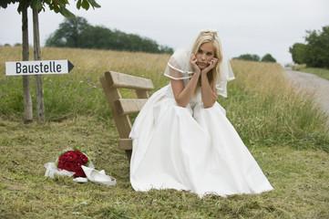 Braut sitzt mit dem Kopf in der Hand und schaut weg.