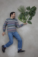 Mann blickt auf die Pflanze in seiner Hand