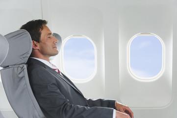 Deutschland, Bayern, München, Geschäftsmann Entspannung in der Business Class Flugzeugkabine