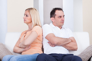 Angry couple sitting on sofa