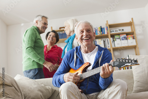 Deutschland, Leipzig, Senior, Rentner spielt E-Gitarre, Mann und Frau im Hintergrund