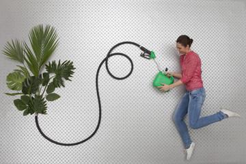 Frau betankt einen Benzinkanister durch Pflanzen