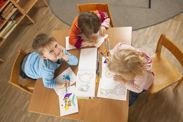 Deutschland, Kinder im Kindergarten sitzen am Tisch, Zeichnen von Bildern