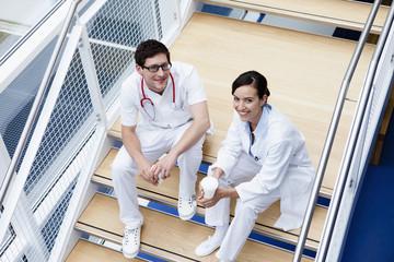Deutschland, Bayern, Diessen am Ammersee, Zwei junge Ärzte sitzen auf Treppe mit Einwegbecher, Lächeln