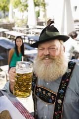 Deutschland, Bayern, Oberbayern, erwachsener Mann im Biergarten hält Steinkrug