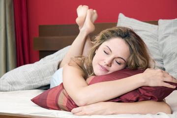 Junge Frau liegt auf dem Bett, die Augen geschlossen