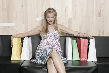Deutschland, Köln, Junge Frau auf der Bank mit Einkaufstüten