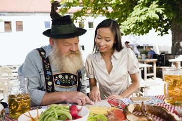 Deutschland, Bayern, Oberbayern, Asiatische Frau und Mann in bayerischer Biergarten