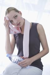 Junge Frau mit Flasche Wasser, Handtuch um den Hals