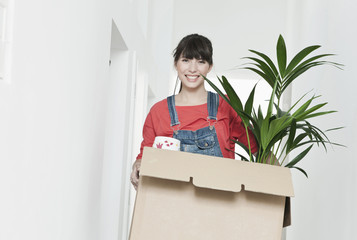 Deutschland, Köln, Junge Frau mit Karton und Pflanzen im Korridor