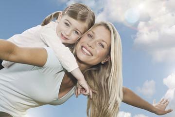 Deutschland, Köln Mutter mit ihrer Tochter auf dem Rücken,