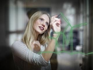 Deutschland, Köln, Junge Frau Zeichnung Windkraftanlage auf Glas