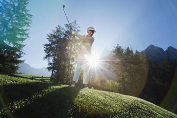 Italien, Kastelruth, erwachsene Frau spielt Golf auf dem Golfplatz