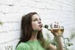 Deutschland, Berlin, Junge Frau trinkt Bier aus Bierflasche