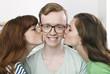 Deutschland, Berlin, Junger Mann bekommt zwei Küsse auf einmal