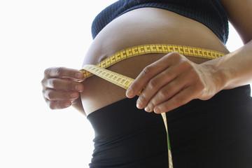 Schwangere Frau misst Bauch mit Maßband